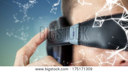 Man using virtual reality glasses against digitally generated background