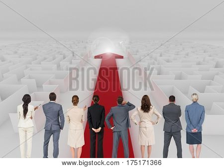 Digital composite image of business executives looking at red arrow through a maze