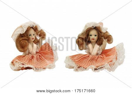 Porcelain doll in pink dress. Isolated porcelain doll in pink dress front and angle view photo.