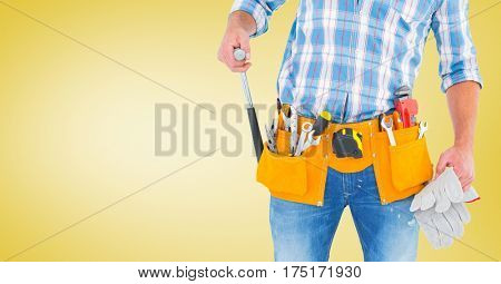 Mid section of handy man standing with tools against yellow background