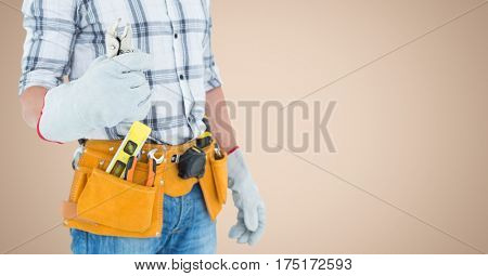 Mid section of handy man standing with tools against beige background