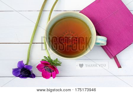 Green tea cup with pink and purple anemones and fuschia note book on white wooden plank table , seen from above , mother's day , thank you gift, relaxing natural drink