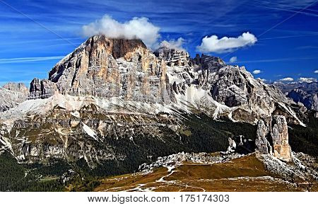 Cinque Torri rock formation and Tofana mountain group from Nuvolau mountain peak in Dolomites mountains in Italy above Passo Falzarego during autumn day with blue sky and only few clouds