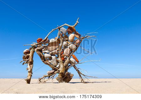 structure of dry twigs and driftwood with colored stones in the desert. Concept of harmony and balance.