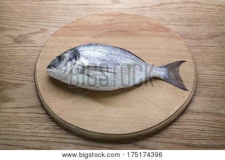 dorado fish on a wooden board top vew