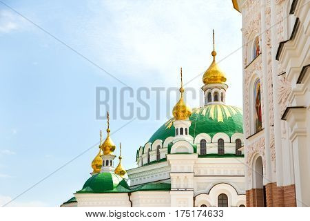 gilded domes against the sky in Kiev Lavra monastery. in the foreground is seen the church wall with stucco Baroque