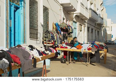 SFAX, TUNISIA - NOVEMBER 30, 2011: Unidentified woman sells secons hand goods at the street in the medina of Sfax, Tunisia.