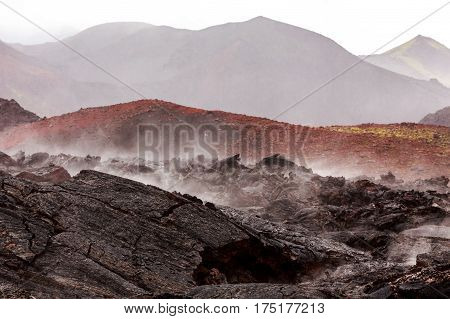 Barren Lava Fields Steaming In Light Rain With Volcanoes In Background