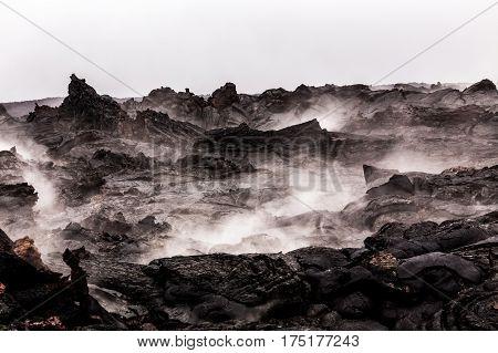 Steaming volcanic lava pieces under light rain