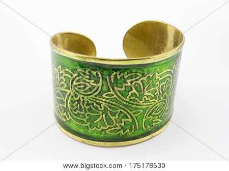 Close up of bold and beautiful green and gold bangle on white background