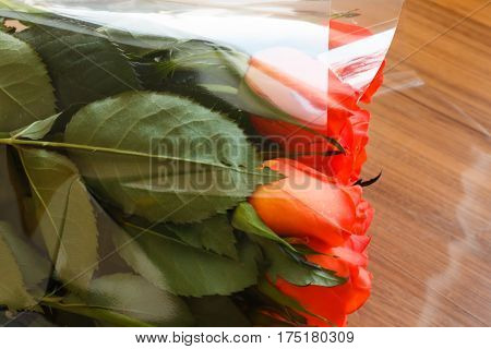 Bouquet Of Orange Roses On A Wooden Table With Reflection