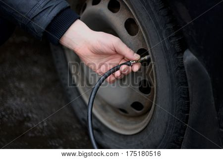 Pumping up the tyres of the car with a special device. Closeup of the hands of the man who pumps up car tires.