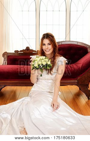 portrait of bride sitting with bouquet of flowers with fainting couch in background