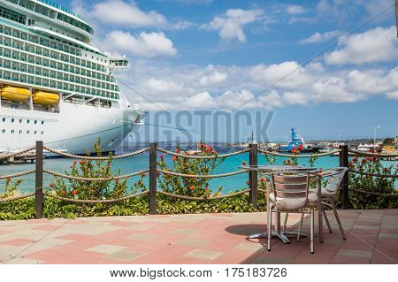 Table on patio of a coastal Caribbean restaurant with a luxury cruise ship in the background