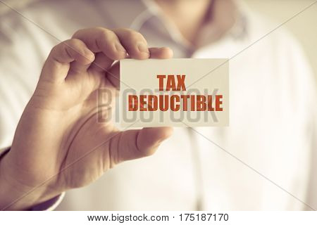Businessman Holding Tax Deductible Message Card