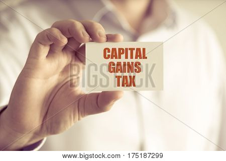 Businessman Holding Capital Gains Tax Message Card