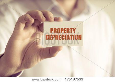 Businessman Holding Property Depreciation Message Card