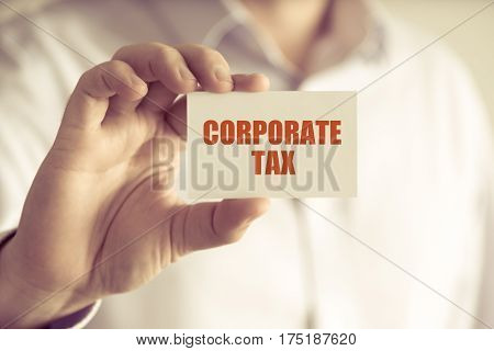 Businessman Holding Corporate Tax Message Card