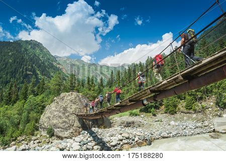 Group of hikers with backpacks go on a suspension bridge over the mountain river. Caucasian mountains Georgia Svaneti region.