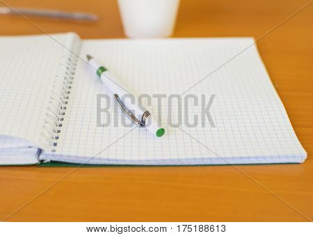 Open notebook with pen for recording lectures on a brown background