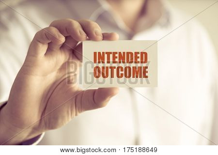 Businessman Holding Intended Outcome Message Card