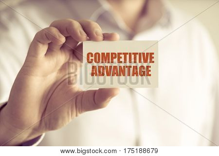 Businessman Holding Competitive Advantage Message Card