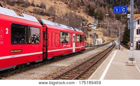 Filisur, Switzerland - 3 March, 2017: a train of the Rhaetian Railway heading to the town of St. Moritz leaving the Filisur railway station. The Rhaetian Railway (Italian: Ferrovia Retica), is a Swiss transport company.