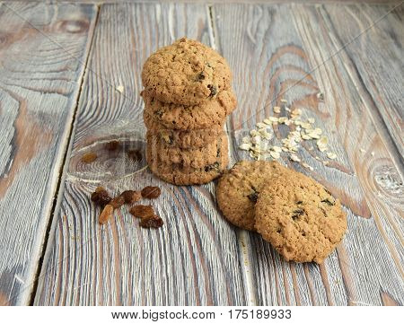 Oatmeal cookies with raisin are on a wooden table.  Cookies are made in house conditions