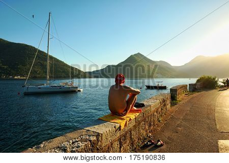 PERAST, MONTENEGRO - JULY 14, 2016: a man in a swimsuit and a red cap is sunbathing at the sunset along the road that crosses the Perast village