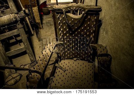 Old medieval torture chamber with a chair and tools