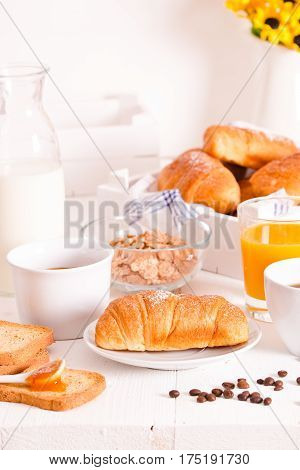 Breakfast with croissants with orange juice on wooden table.