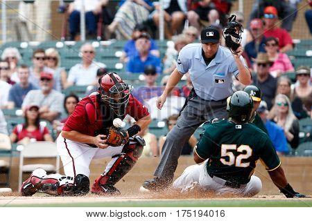 Arizona Diamondbacks catcher Miguel Montero (26) misses the tag on Oakland Athletics outfielder Yoenis Cespedes at Salt River Fields at Talking Stick on March 6, 2014 in Scottsdale, Arizona.