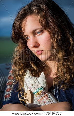 Portrait of lonely young woman looking sad holding stuffed cat toy