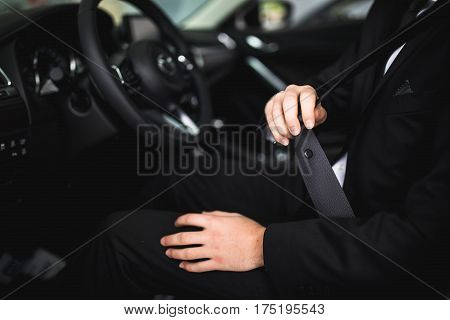 Close-up of man sitting in car fastening seat belt with hands