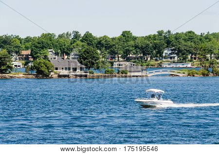 Kingston, Canada - July 24, 2014: Boat swimming on Saint Lawrence river in the Thousand Islands on the Canadian side of the archipelago