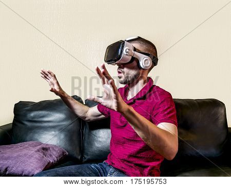 The man in glasses virtual reality plays on the black sofa