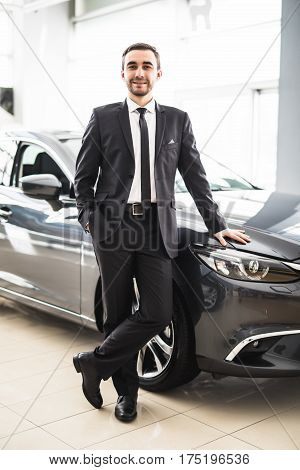 Professional salesman smiling in front of a new car at the dealership profession occupation job owning buy retail luxury lifestyle concept