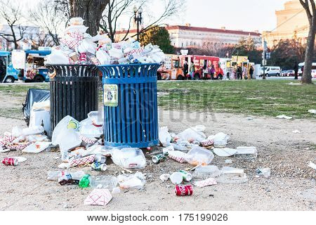 Washington DC USA - January 28 2017: Overflowing trash bins in National Mall with people eating by food trucks