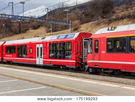Filisur, Switzerland - 3 March, 2017: a train of the Rhaetian Railway at a platform of the Filisur railway station. The Rhaetian Railway (German: Rhatische Bahn, abbreviated as RhB), is a Swiss transport company.