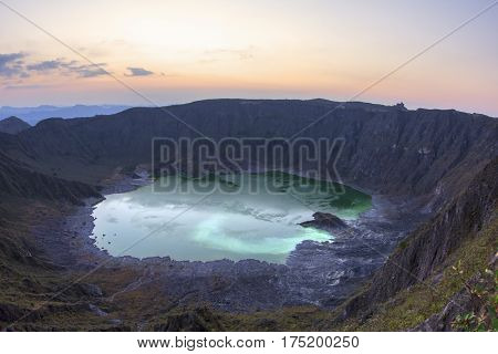 Acidic green sulfuric lake at bottom of crater at El Chichonal volcano soon after sunset in Chiapas Mexico