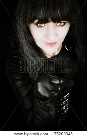 Attractive mature woman pointing finger with gloved hand wearing black and with amber cats eyes. With a black background. Manipulated effects for reprimand from a cougar concept
