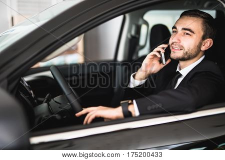 Portrait handsome business man use phone in car