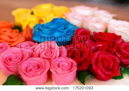 detail of colored marzipan roses on birthday cake