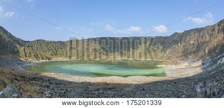 Panoramic interior of El Chichonal volcano with green sulfuric lake in crater and active fumaroles on sunny day in Chiapas Mexico