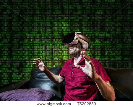 The man in glasses virtual reality plays on digital background matrix