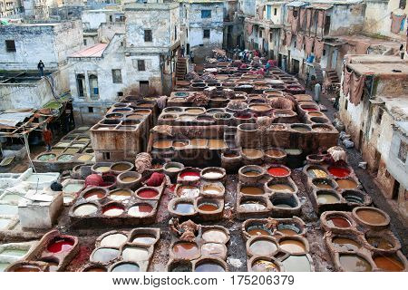 FEZ, MOROCCO - JANUARY 4, 2014: Men working hard in the tannery souk