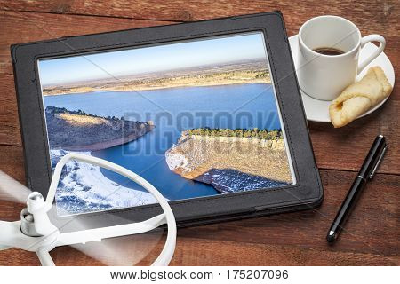 aerial photography concept - reviewing aerial pictures of the Horsetooth Reservoir on  a digital tablet with a drone rotor and coffee, screen picture copyright by the photographer
