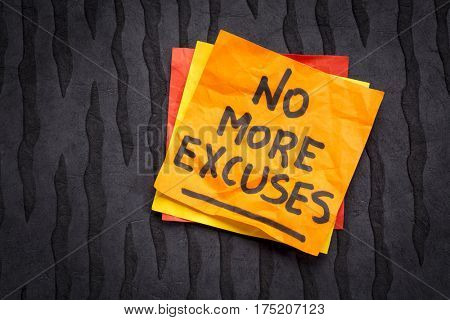 No more excuses! A motivational handwriting on a sticky note against black lokta paper