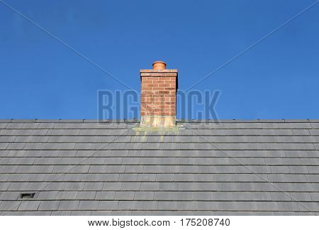 Gray tile roof and chimney on house with blue sky background.