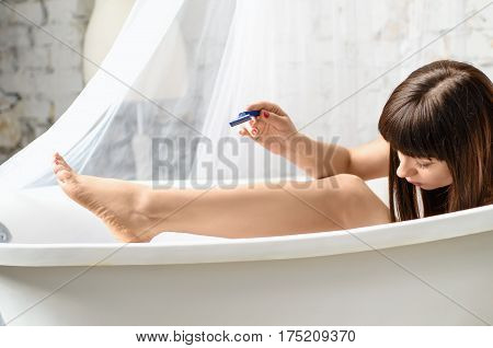 Woman shaving legs with razor blade in bath. Hair removal. Skin damage, scratch. Woman shaving legs in bathroom. Hand with using a razor for woman's leg. Smooth-shaven legs.